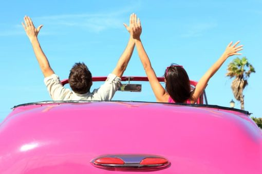 couple in covertible car with hands in the air